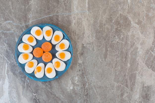 Bovenaanzicht van zoete verse snoepjes op blauwe houten bord.