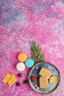 Bovenaanzicht van zoete wafels met macarons op lichtroze oppervlak