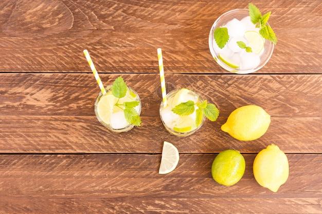 Bovenaanzicht van zomer verkoelende dranken op houten tafel. coolig verse limonade met limoen, citroen, muntblaadjes en ijs.