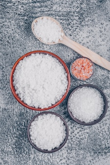 Bovenaanzicht van zout in glas, kommen en houten lepel met himalaya zout