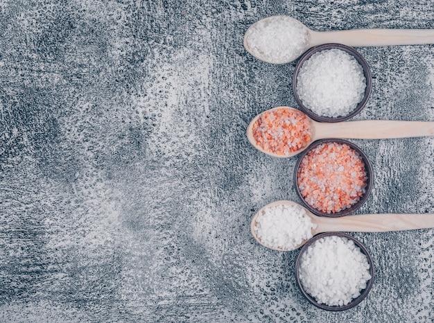 Bovenaanzicht van zout in kommen en houten lepels met himalaya zout