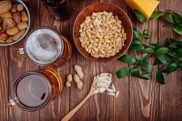 Bovenaanzicht van zoute snackpinda's in een kom en zonnebloemzaad in een houten lepel met twee mokken bier op rustiek hout
