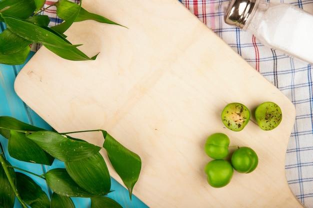 Bovenaanzicht van zure groene pruimen en een zoutvaatje op een houten snijplank met ruscus bladeren op geruite stoffen tafel