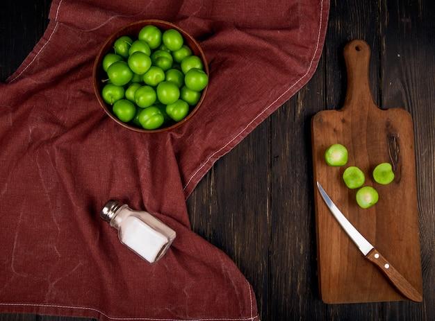 Bovenaanzicht van zure groene pruimen in een kom en gesneden pruimen op een houten snijplank met mes en een zoutvaatje op donkere rustieke tafel