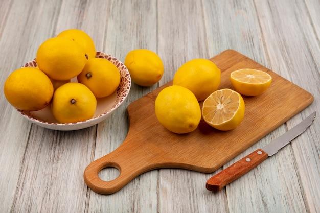 Bovenaanzicht van zure hele citroenen op een kom met citroenen geïsoleerd op een houten keukenplank met mes op een grijs houten oppervlak