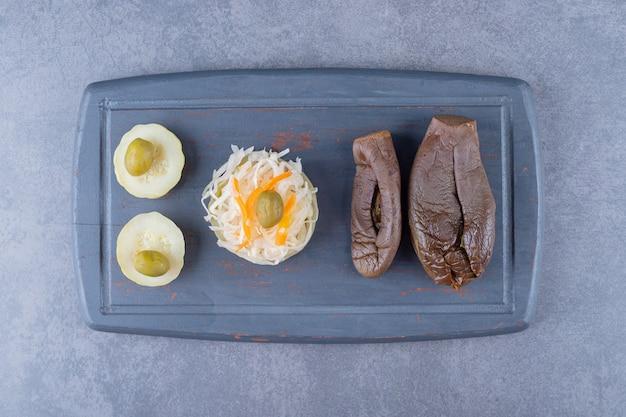 Bovenaanzicht van zuurkool met gevulde aubergine augurk op grijs houten bord.