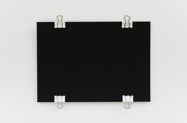 Bovenaanzicht van zwart papier met metalen clips aan de zijkanten