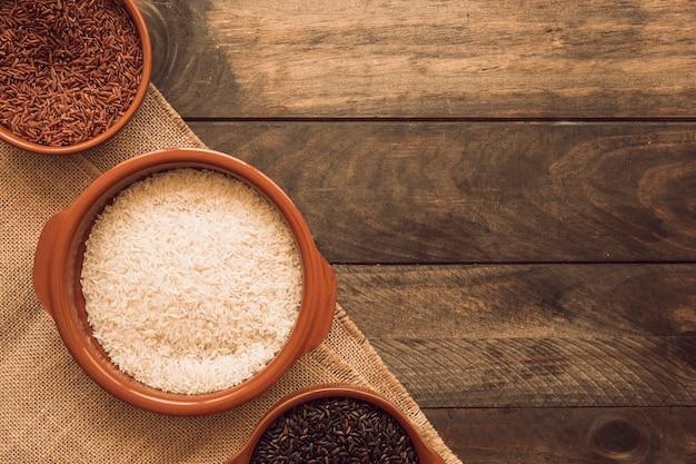 Bovenaanzicht van zwart; rode en witte organische rijstkorrels op jutedoek over de houten lijst