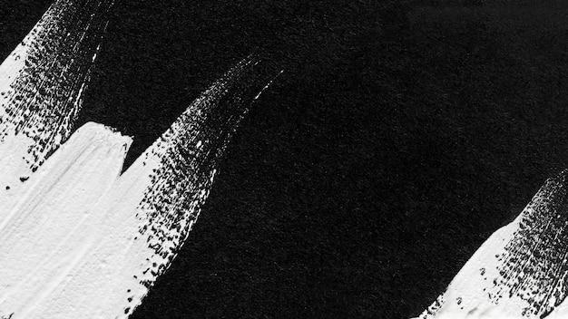 Bovenaanzicht van zwart-wit verf penseelstreken op het oppervlak