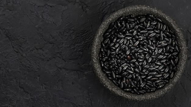 Bovenaanzicht van zwarte bonen in kom met kopie ruimte