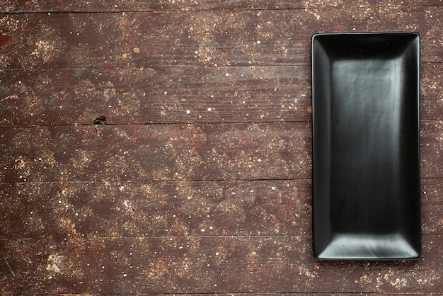 Bovenaanzicht van zwarte cakevorm langgevormd de bruine rustiek, cake eten bak zoet bureau, hout