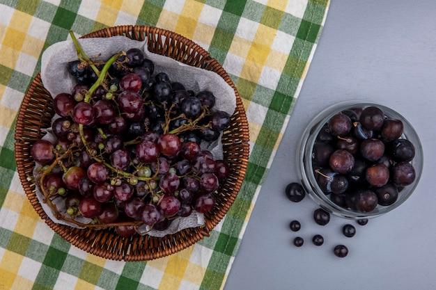 Bovenaanzicht van zwarte druif in mand op geruite doek en druiven bessen in kom op grijze achtergrond