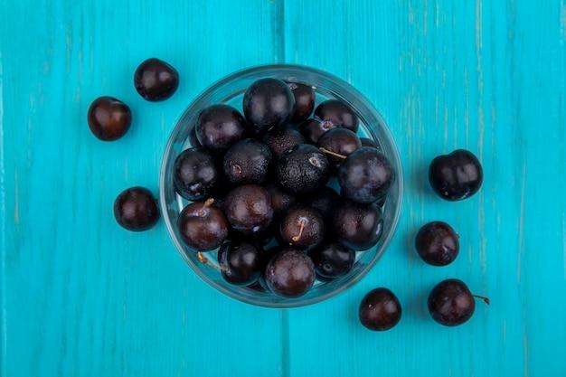 Bovenaanzicht van zwarte druiven bessen in kom en op blauwe achtergrond