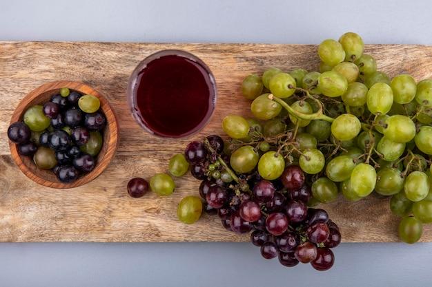 Bovenaanzicht van zwarte druivensap in glas en druiven in kom en op snijplank op grijze achtergrond