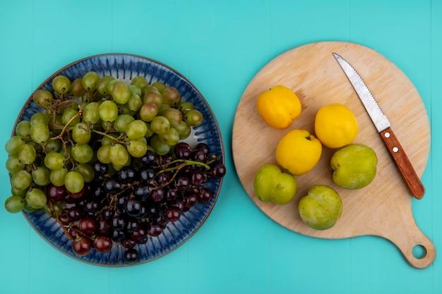 Bovenaanzicht van zwarte en witte druiven in plaat en groene plukken abrikozen met mes op snijplank op blauwe achtergrond