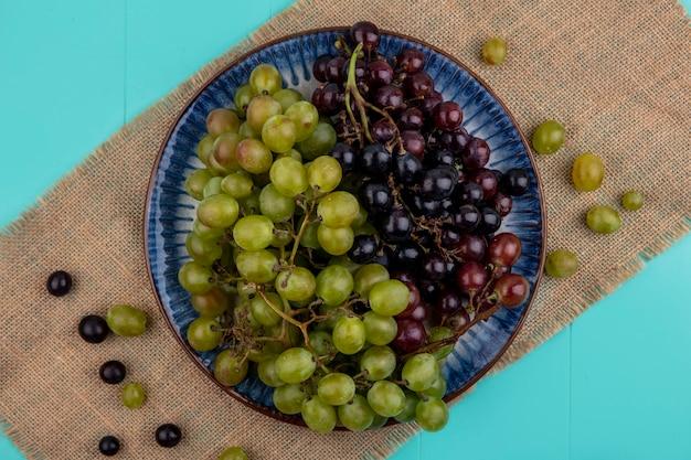 Bovenaanzicht van zwarte en witte druiven in plaat op zak op blauwe achtergrond