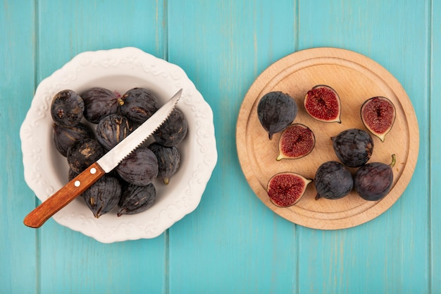 Bovenaanzicht van zwarte missie vijgen op een houten keuken bord zwarte vijgen op een kom met mes op een blauwe houten muur