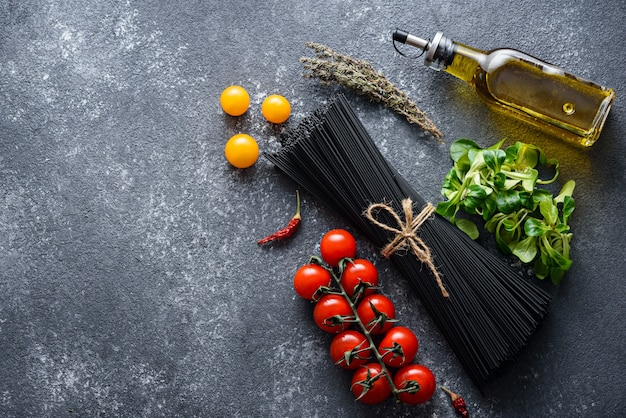 Bovenaanzicht van zwarte pasta, tomaten, olijfolie, sla, chilipepers op grijze achtergrond met kopie ruimte, koken diner concept