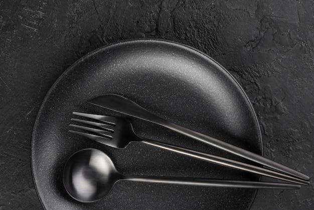 Bovenaanzicht van zwarte plaat met bestek