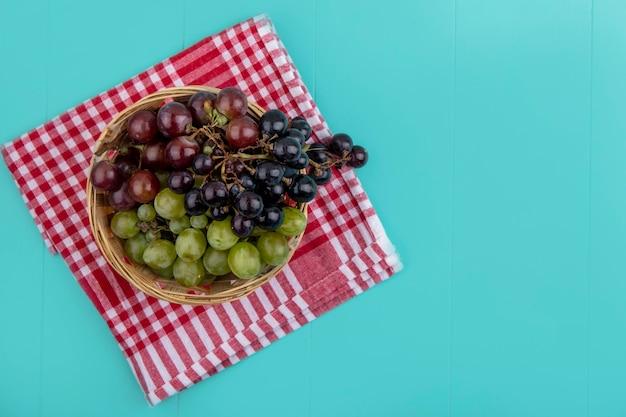 Bovenaanzicht van zwarte rode en witte druiven in mand op geruite doek op blauwe achtergrond met kopie ruimte