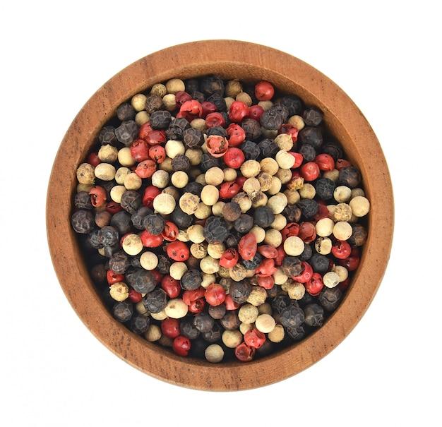 Bovenaanzicht van zwarte, rode en witte peper in houten kom