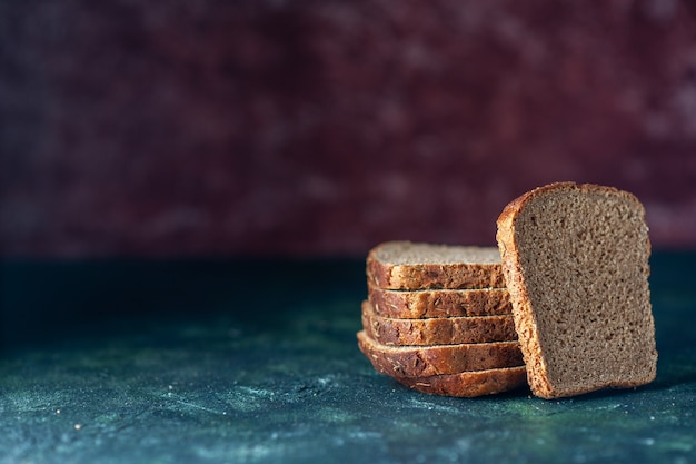 Bovenaanzicht van zwarte sneetjes brood aan de linkerkant op een achtergrond met gemengde kleuren met vrije ruimte