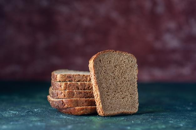 Bovenaanzicht van zwarte sneetjes brood op gemengde kleuren achtergrond met vrije ruimte