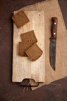 Bovenaanzicht van zwarte sneetjes brood op snijplank met mes op zak op kastanjebruine achtergrond