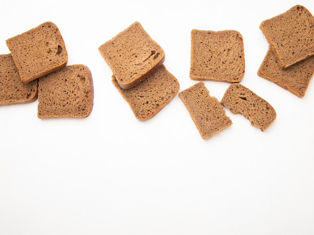 Bovenaanzicht van zwarte sneetjes brood op witte achtergrond met kopie ruimte