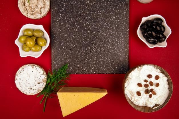 Bovenaanzicht van zwarte snijplank en ingelegde olijven glas melk kwark in een kom geit en nederlandse kaas rond gerangschikt op rood