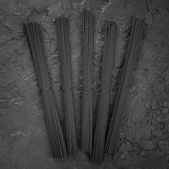 Bovenaanzicht van zwarte spaghetti bundels op leisteen