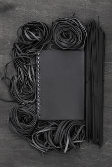 Bovenaanzicht van zwarte spaghetti en tagliatelle met laptop