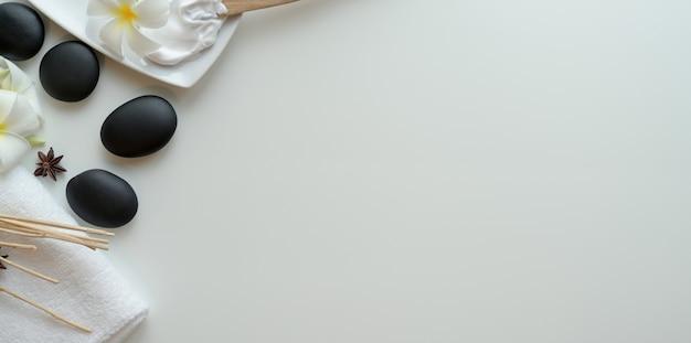Bovenaanzicht van zwarte stenen en accessoires voor massages op wit