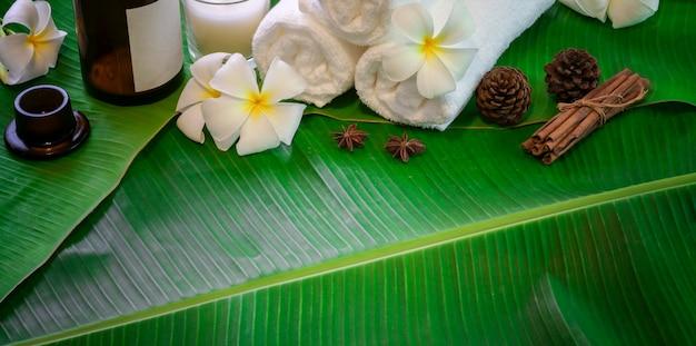 Bovenaanzicht van zwarte stenen en handdoeken voor massages op groene bananenbladeren