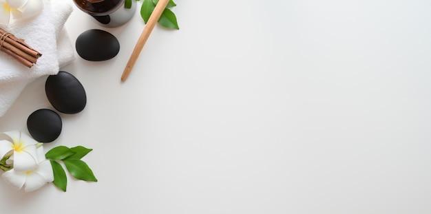 Bovenaanzicht van zwarte stenen en handdoeken voor massages op witte achtergrond