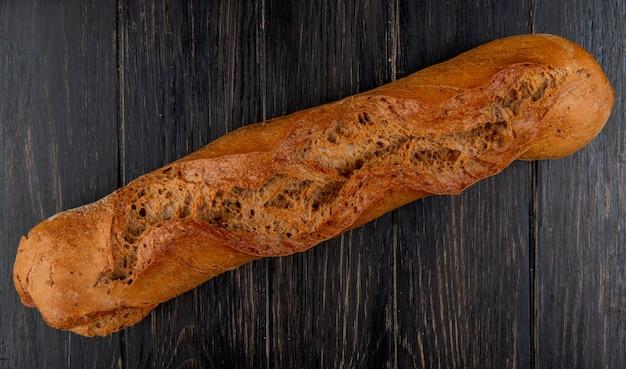 Bovenaanzicht van zwarte stokbrood op houten tafel