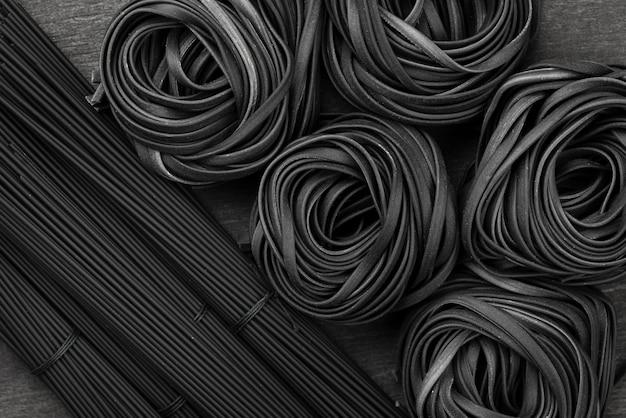 Bovenaanzicht van zwarte tagliatelle en spaghetti
