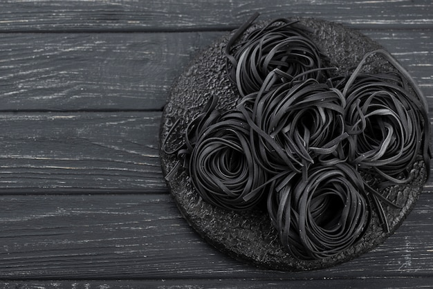 Bovenaanzicht van zwarte tagliatelle op plaat