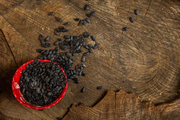 Bovenaanzicht van zwarte zonnebloempitten verspreid uit een kom op hout