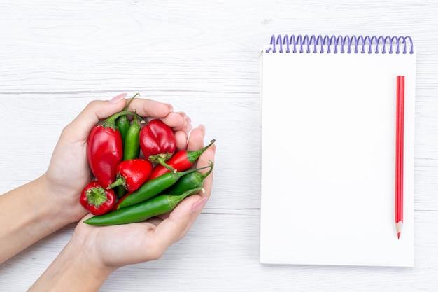 Bovenaanzicht vaned paprika's pittige greep door vrouwtje met blocnote op lichte, plantaardige hete pittige maaltijd rauw
