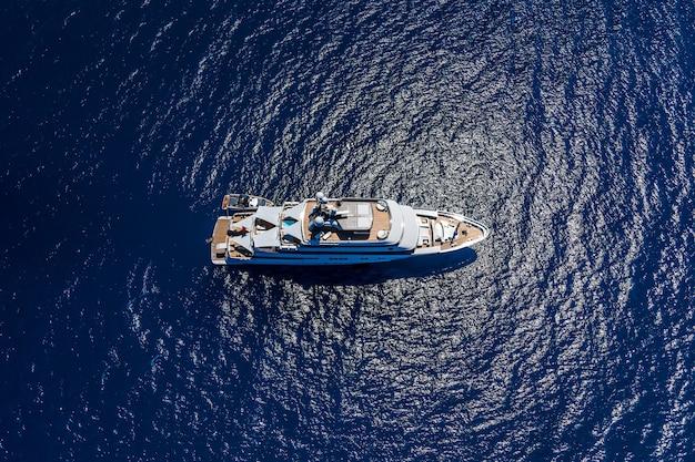 Bovenaanzicht vanuit de lucht gemaakt door drone van groot jacht in de blauwe zee.