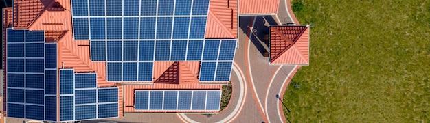 Bovenaanzicht vanuit de lucht van een nieuw modern woonhuis met blauwe panelen. hernieuwbaar ecologisch groen energieproductieconcept.