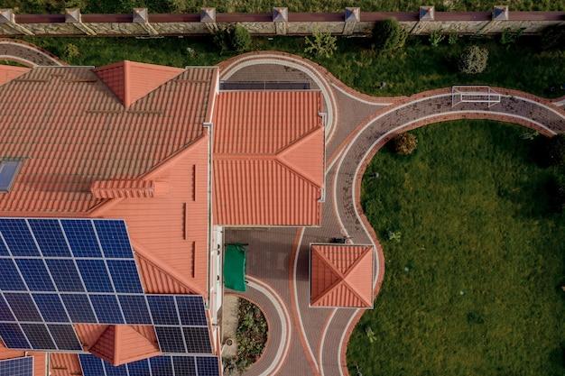 Bovenaanzicht vanuit de lucht van een nieuw modern woonhuis met blauwe panelen. hernieuwbaar ecologisch groene energieproductieconcept.
