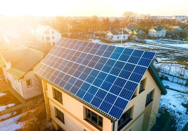 Bovenaanzicht vanuit de lucht van een nieuw, modern woonhuis met twee verdiepingen en een blauw glanzend fotovoltaïsch zonnepaneelsysteem op het dak. hernieuwbaar ecologisch groen energieproductieconcept.