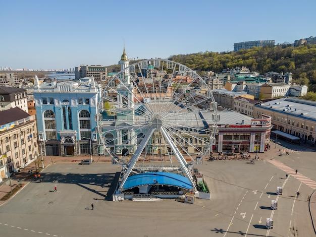 Bovenaanzicht vanuit de lucht van het stadsbeeld van kiev en het kontraktova-plein met reuzenrad in de stad kiev