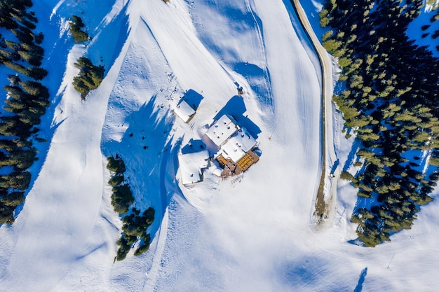 Bovenaanzicht vanuit de lucht van kleine huizen op een besneeuwde berg omringd door bomen bij daglicht