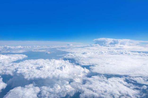 Bovenaanzicht vanuit het vliegtuigraam op prachtige cumulus pluizige witte wolken op een blauwe lucht met een felle zon. perfecte abstracte hemelachtergrond, behang, lay-out.