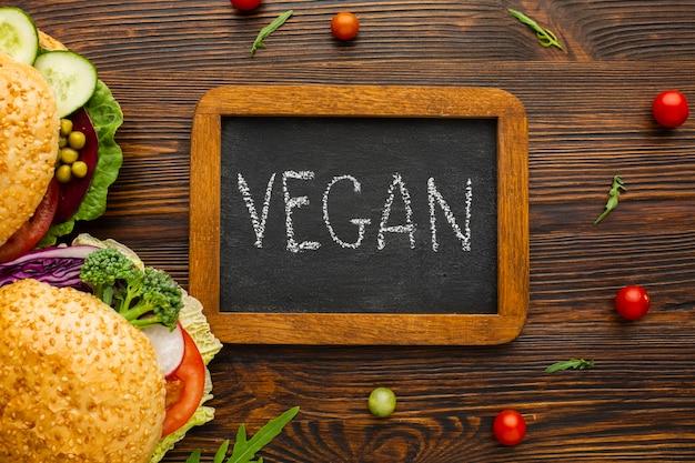 Bovenaanzicht vegan belettering op schoolbord met houten achtergrond