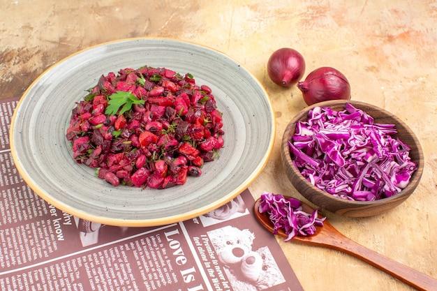 Bovenaanzicht veganistische salade met groene bladeren en groenten op een grijs gekleurd bord met kom gehakte kool en uien op een houten tafel