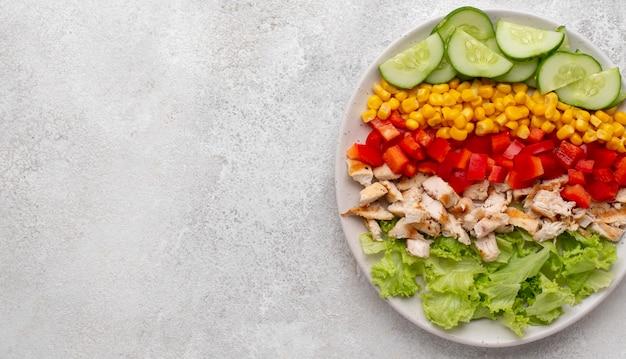 Bovenaanzicht vegetarische salade met kip en kopie-ruimte